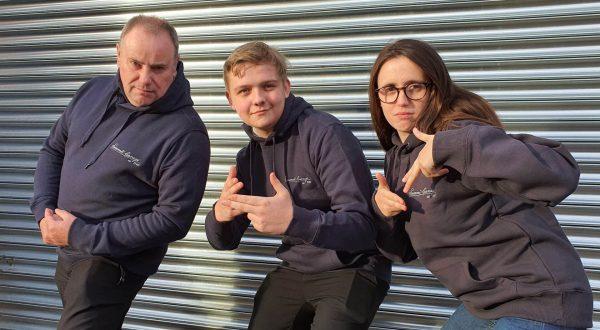The Summit Garage team wearing the 'Original' Summit Garage Hooded Sweatshirt